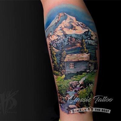 Альпийский пейзаж в стиле реализм - тату на голени девушки