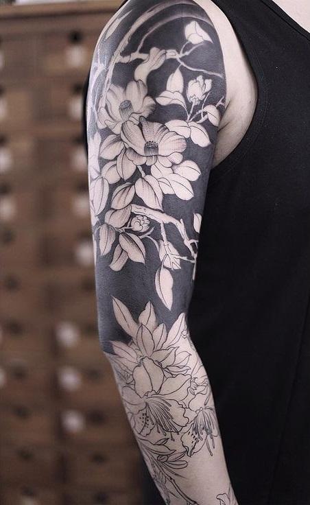 Мужское тату на руке с элементами Blackwork и цветами