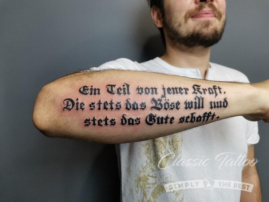 Тату-надпись в готическом стиле на предплечье у мужчины