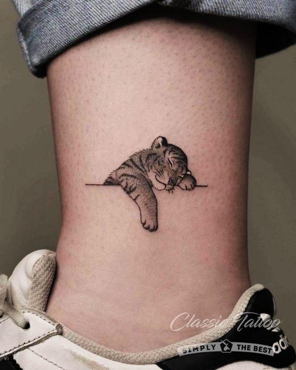 Черная татуировка на ноге в виде тигренка