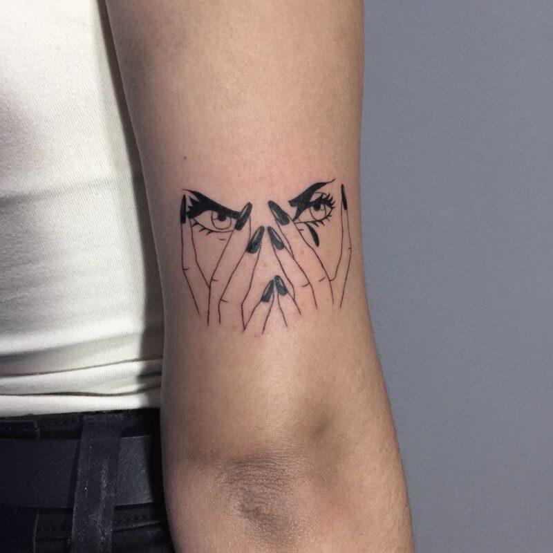 Черная татуировка на руке девушки в виде пальцев прячущих лицо
