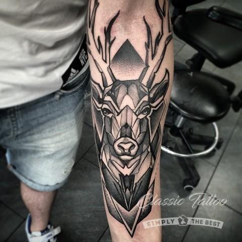 Черная татуировка на руке в стиле абстракции с изображением оленя