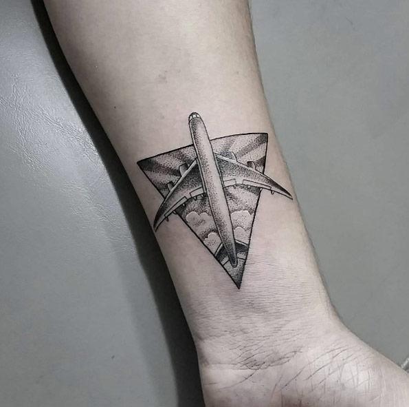 Черная маленькая татуировка на руке мужчины в виде самолета