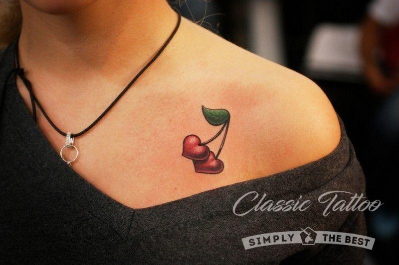 Цветная татуировка на ключице девушки в виде сердечек