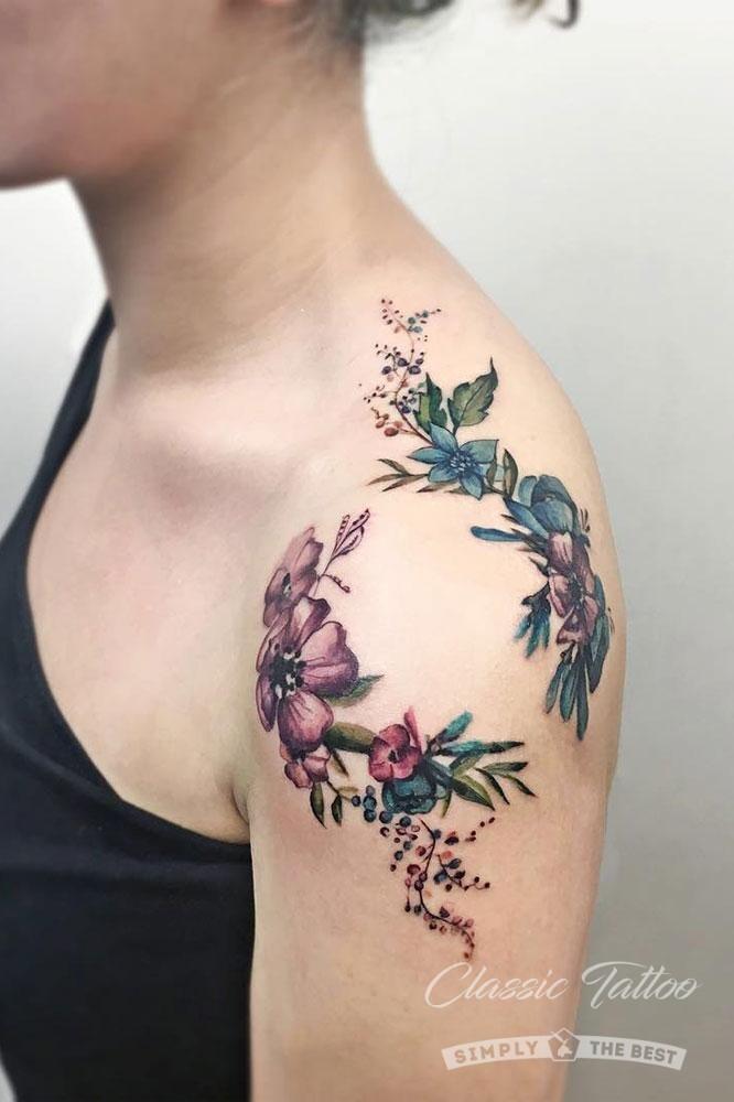 Цветная татуировка на плече девушки в виде цветов