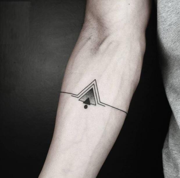 Черное тату на руке мужчины в виде гор из геометрии