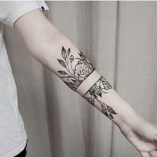 Черное тату на руке в виде цветов