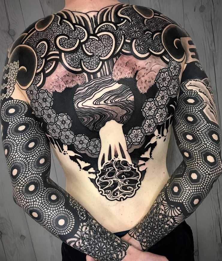 Черная татуировка на руках и спине мужчины в стиле абстракция
