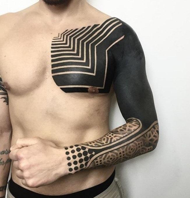 Черное тату на руке мужчины в стиле blackwork