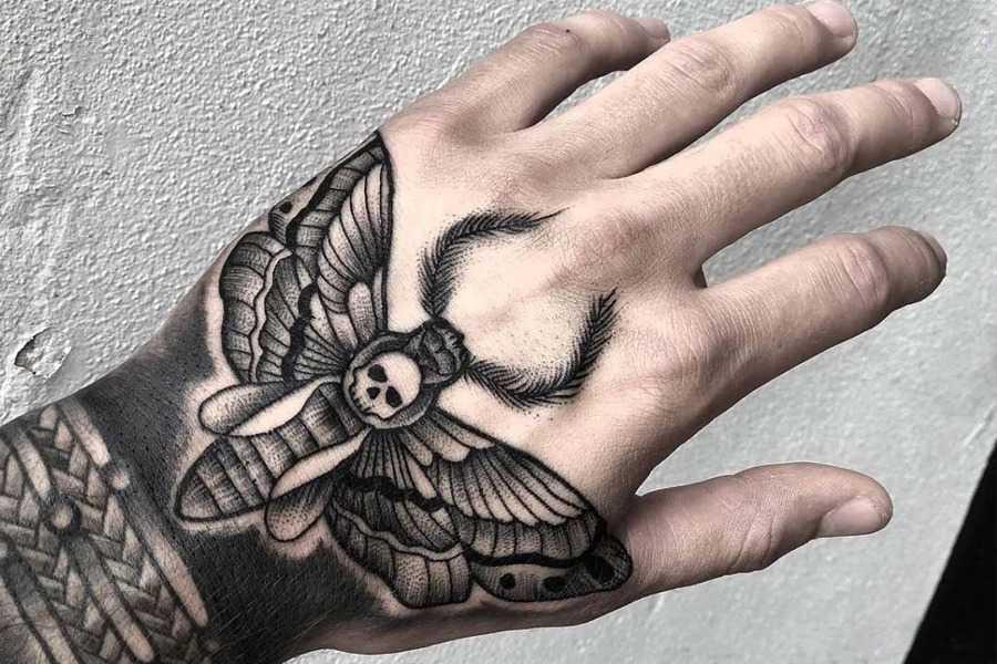Мужское черно-белое тату на руке бражник мертвая голова в стиле дотворк