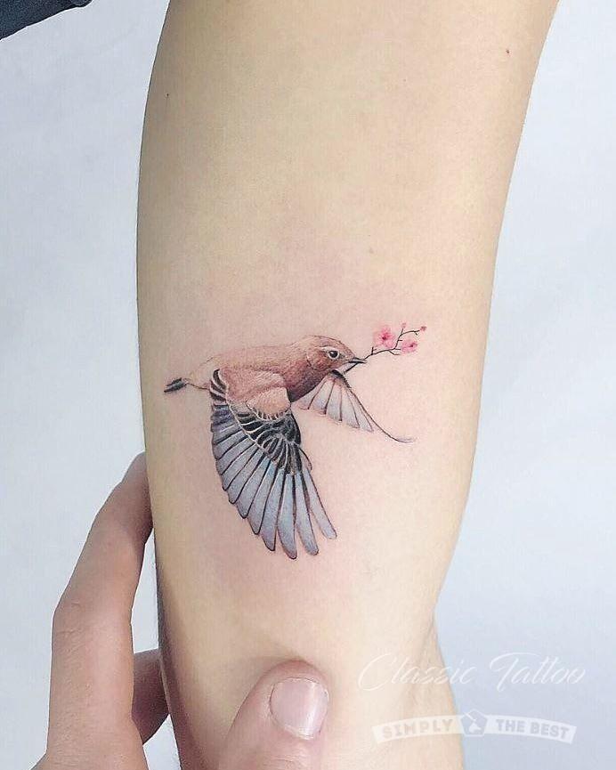 цветное женское тату на руке воробей с веткой сакуры реализм