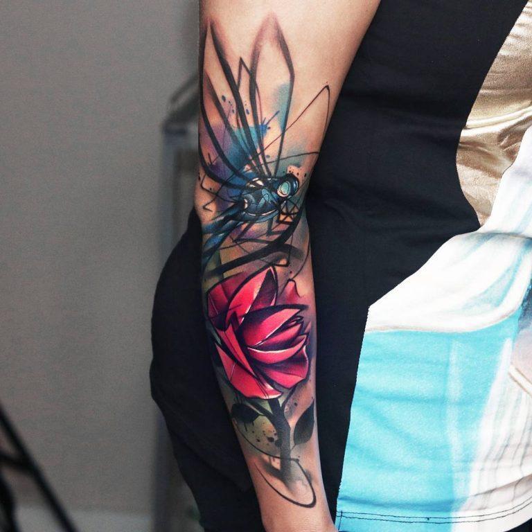 Стрекоза и роза цветное сюрреалистичное тату на руке женщины