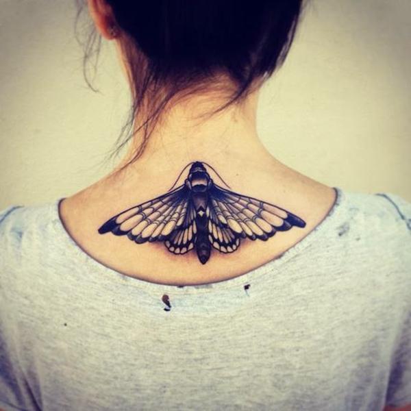 Черная татуировка на спине девушки в виде бабочки