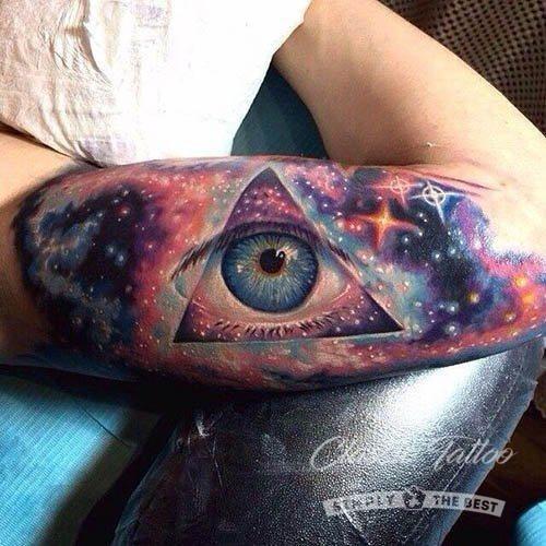 Глаз внутри галактики - красочное реалистичное мужское тату на руке