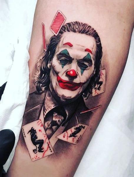 Красочное тату портрет Джокера на предплечье мужчины