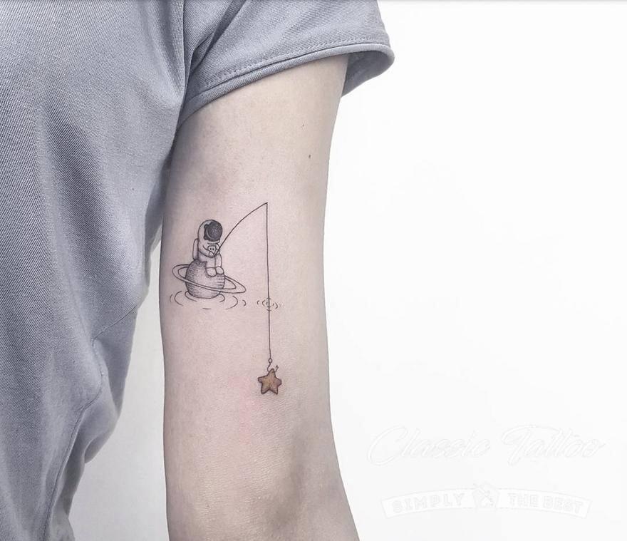 Тату в стиле минимализм - космонавт-рыбак на Сатурне