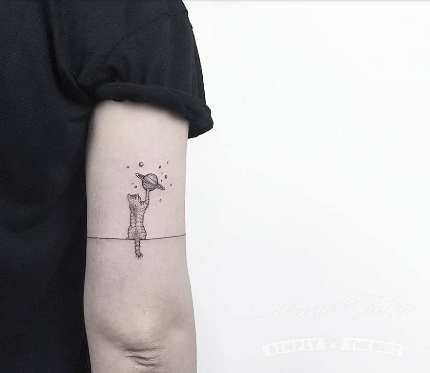 Черно-белое тату в стиле минимализм для девушки - кот играет с Юпитером