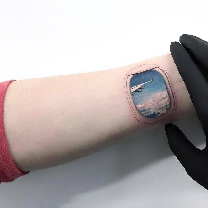 Цветное маленькое тату иллюминатор на руке у девушки