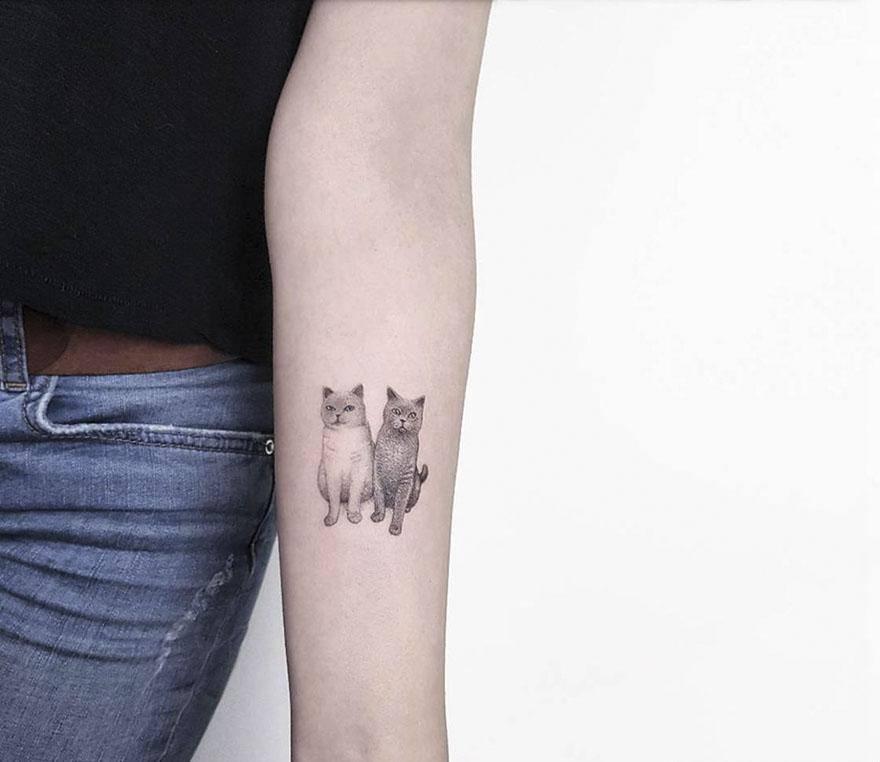 Монохромное тату в стиле минимализм для девушки на предплечье британские кошки
