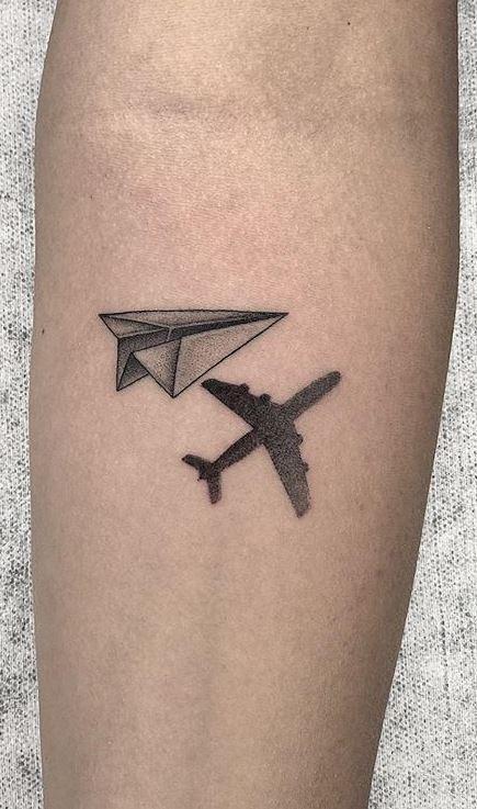 Бумажный и настоящий самолет - маленькая тату на руке мужчины в стиле минимализм