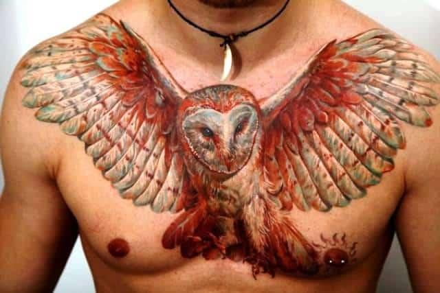 Мужское тату сова в стиле реализм на груди мужчины