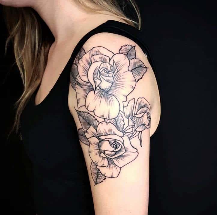 Тату розы на плече у девушки в черном цвете