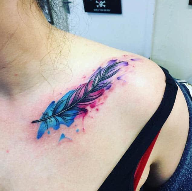 Цветная акварельная татуировка для девушки на ключице перо