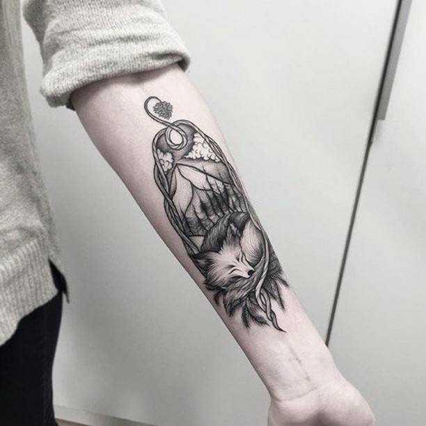 Спящая лиса на фоне горного пейзажа - монохромная тату у девушки на предплечье