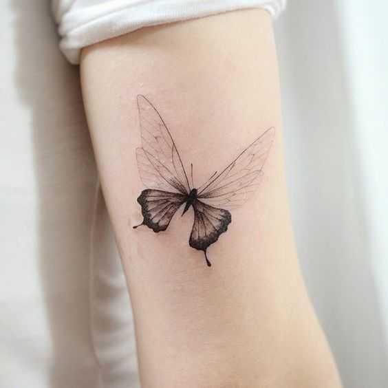 Бабочка парусник - маленькое тату в черном цвете на руке девушки