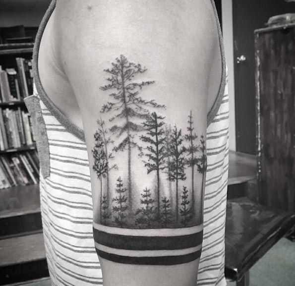 Тату на руке у мужчины хвойный лес в стиле блэкворк