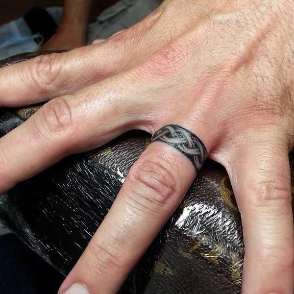 Татуировка на пальце мужская кольцо орнамент в черном цвете