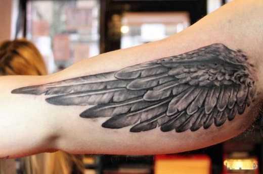 Тату крыло в стиле реализм в черном цвете на руке мужчины