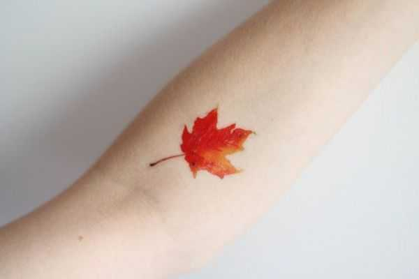Яркое акварельное тату кленовый лист на руке девушки